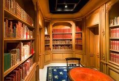Livros velhos em estantes com volumes e na tabela de madeira antiga dentro da biblioteca fotografia de stock royalty free