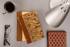 Livros velhos em uma mesa moderna com uma xícara de café Fotos de Stock Royalty Free
