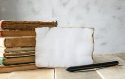 Livros velhos na tabela Uma folha de papel branca queimada em torno das bordas Lugar para seu texto imagem de stock royalty free