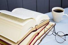 Livros velhos, vidros e copo de café abertos no fundo de madeira foto de stock