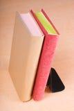 Livros vermelhos e dourados que inclinam-se no suporte para livros Fotografia de Stock