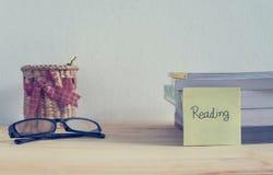 Livros, vidros e pena da caixa na tabela Foto de Stock