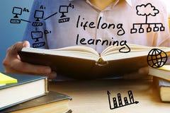 Livslångt begrepp för lära Man som läser boken arkivfoto