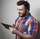 Livsstil, folk och utbildningsbegrepp: man att lyssna till audiobook till och med hörlurar på vit bakgrund Arkivbilder