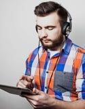 Livsstil, folk och utbildningsbegrepp: man att lyssna till audiobook till och med hörlurar på vit bakgrund Arkivfoto