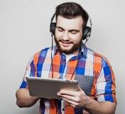 Livsstil, folk och utbildningsbegrepp: man att lyssna till audiobook till och med hörlurar på vit bakgrund Fotografering för Bildbyråer