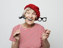 Livsstil och folkbegrepp: den roliga farmodern med fejkar mustaschen och exponeringsglas, skratt och förbereder sig för parti arkivfoto