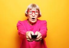 Livsstil och folkbegrepp: den roliga farmodern rymmer en TV avlägsen över gul bakgrund arkivfoton