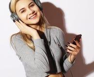 Livsstil och folkbegrepp: Härlig ung kvinna som lyssnar till arkivbild