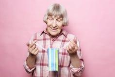 Livsstil och folkbegrepp: Lycklig hög kvinna med shoppingpåsen över rosa bakgrund royaltyfri foto