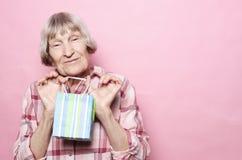 Livsstil och folkbegrepp: Lycklig hög kvinna med shoppingpåsen över rosa bakgrund royaltyfria bilder