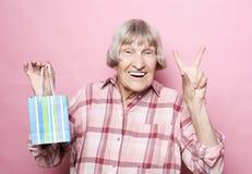 Livsstil och folkbegrepp: Lycklig hög kvinna med shoppingpåsen över rosa bakgrund arkivfoto