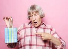 Livsstil och folkbegrepp: Lycklig hög kvinna med shoppingpåsen över rosa bakgrund royaltyfria foton