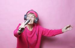 Livsstil och folkbegrepp: Rolig lyssnande musik för gammal dam med hörlurar och sjunga med mic royaltyfria bilder