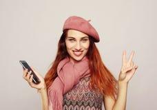 Livsstil och folkbegrepp: St?ende av en tillfredsst?lld tillf?llig flickainnehavmobiltelefon och uppvisning av ok gest royaltyfri foto