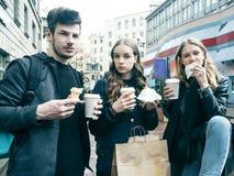 Livsstil och folkbegrepp: tv? flickor och grabb som ?ter snabbmat p? stadsgatan som har tillsammans gyckel som dricker kaffe royaltyfri fotografi