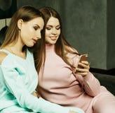 Livsstil och folkbegrepp: Tv? h?rliga kvinnor som hemma ser mobiltelefonen royaltyfri foto