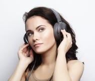 Livsstil och folkbegrepp: Ung kvinna med hörlurarliste Arkivbild