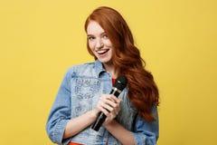 Livsstil och folkbegrepp: Uttrycksfull flicka som sjunger med en mikrofon, isolerad ljus gul bakgrund royaltyfria bilder