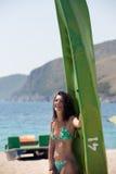 livsstil, sommarferier och semesterbegrepp Kvinna som står den near kajaken, kajakkonkurrens, skrattar och har gyckel på beacen royaltyfri foto