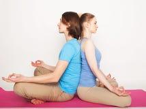 Livsstil-, sport- och folkbegrepp: Barnpar i yoga poserar royaltyfri foto