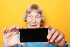 Livsstil-, tehnology- och folkbegrepp: mormodern i blå tröja ler och tar en selfie arkivbilder