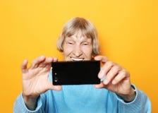 Livsstil-, tehnology- och folkbegrepp: mormodern ler och tar en selfie över gul bakgrund arkivfoto