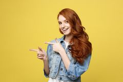 Livsstilbegrepp: Lycklig upphetsad cuacaisan turist- flicka som pekar fingret på kopieringsutrymme som isoleras på guld- guling royaltyfri foto