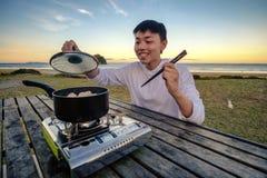 Livsstilbild av den unga lyckliga asiatiska mannen som äter den varma krukaugnen på en tabell som är utomhus- längs stranden Frit royaltyfri foto