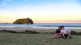 Livsstilbild av unga asiatiska par som sitter på gräsfält längs kust med solnedgånghimmel fotografering för bildbyråer