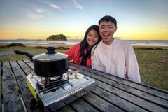 Livsstilbild av unga lyckliga asiatiska par som äter den varma krukaugnen på en tabell som är utomhus- längs stranden Fritidsakti royaltyfri bild