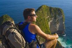 Livsstildet friastående av den unga attraktiva och stiliga mannen med den trekking strandklippan för ryggsäck som ser det här royaltyfri bild