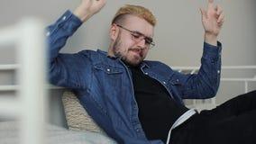Livsstilfors av den unga attraktiva millenial mannen med stilfull frisyr som spelar leken på smartphonen i vit säng lager videofilmer