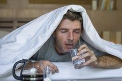 Livsstilhemstående av den unga utmattade och slösade mannen som vaknar upp att lida huvudvärk och bakrus, når att ha druckit alko arkivbilder