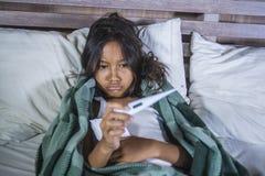 Livsstilhemstående av unga härliga och söta 8 år gammalt för innehavtermometer för kvinnligt barn som ligga är sjukt på säng som  arkivbild
