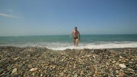 Livsstilmannen går in i havet på ett Pebble Beach och bad på vågen arkivfilmer