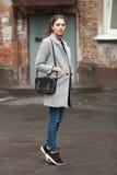 Livsstilmodestående av den härliga unga brunettkvinnan i grå färglag med den svarta läderpåsen som poserar på molnig dag för gata Fotografering för Bildbyråer