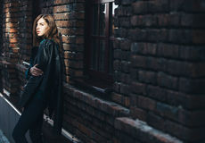 Livsstilmodeståenden av brunettflickan vaggar in svart stil, stående det fria i stadsgatan arkivfoto