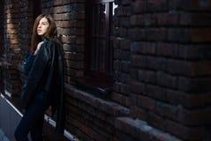 Livsstilmodeståenden av brunettflickan vaggar in svart stil, stående det fria i stadsgatan arkivfoton