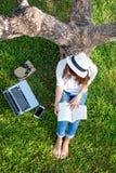 Livsstilpersonflickan tycker om lyssnande musik, och läsning en bok och en lekbärbar dator på gräsfältet av naturen parkerar i mo royaltyfria foton