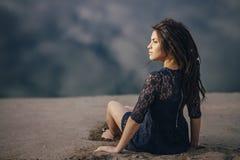 Livsstilstående av brunetter för en kvinna i bakgrund av sjösammanträde i sand på en molnig dag Romantiker försiktigt som är myst royaltyfria foton