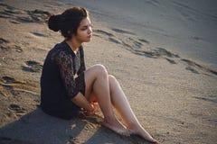 Livsstilstående av brunetter för en kvinna i bakgrund av sjösammanträde i sand på en molnig dag Romantiker försiktigt som är myst royaltyfri fotografi