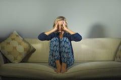 Livsstilstående av den attraktiva och ledsna kvinnan med couc för soffa för frustrerat och angeläget sammanträde för huvudvärk- o arkivfoton