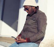 Livsstilstående av den stilfulla unga afrikanska mannen som använder smartphonen i stad Fotografering för Bildbyråer