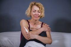 Livsstilstående av den unga desperata gravida kvinnan som använder den deprimerad graviditetstestet som är ledsen och för att för arkivfoto