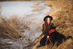 Livsstilstående av den unga kvinnan i svart hatt med hennes hund som vilar vid sjön på en trevlig och varm höstdag royaltyfri fotografi