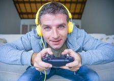 Livsstilstående av den unga lyckliga och upphetsade gamermannen med hörlurar som hemma som spelar videospelet har gyckel på soffa royaltyfri foto