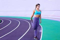 Livsstilstående av den unga och idrotts- flickan som gör uppvärmning och genomkörare och sträckning royaltyfri bild