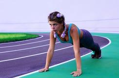 Livsstilstående av den unga och idrotts- flickan som gör uppvärmning och genomkörare och sträckning fotografering för bildbyråer
