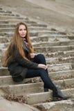 Livsstilstående av den unga och nätta vuxna kvinnan med ursnyggt långt hår som poserar sammanträde på den konkreta trappan som se arkivfoto